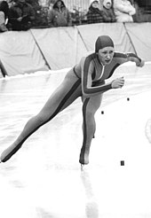 A woman is wearing a skin-tight jumpsuit with a hood and ice skates; she is making a turn as she skates on an ice track.