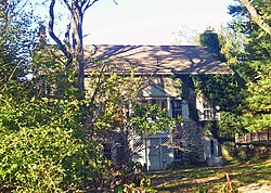 A stone house with some ivy on the front and a triangular-roofed rear wooden porch partially obscured by shrubbery on the left