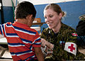 Canadian Forces Capt. Karoline Martin, a nurse with the Canadian Forces Health Services Center, gives a child a sticker after an examination during a medical clinic April 15, 2013, in Caluco, El Salvador, as 130415-Z-SF323-051.jpg