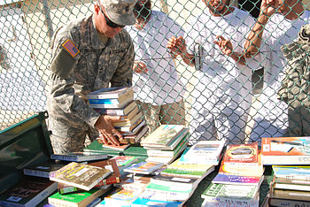 English: GUANTANAMO BAY, Cuba - A Joint Task Force Guantanamo Trooper displays reading materials from the JTF library for detainees to choose from Nov. 18, 2008. Detainees regularly choose from the library's holdings of 8,000 books and magazines in English, Pashtu and Arabic. (JTF Guantanamo photo by Navy Petty Officer 2nd Class Patrick Thompson)