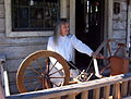 Charlene Parker demonstrating how thread or yarn is tranferred from a spinning wheel to a clock reel..jpg