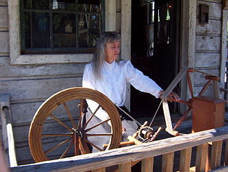 Spinner's weasel - Knott's Berry Farm spinner Charlene Parker demonstrates how to transfer thread or yard from a spinning wheel (on left) to a spinner's weasel (on right).