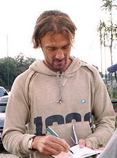 Unshaven white man with scruffy hair wearing a casual hooded top signs autographs