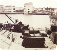 An old photograph showing piles of construction materials and equipment along the bank of a river with large white buildings lining the opposite bank