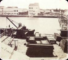 Uma fotografia de idade mostrando pilhas de materiais e equipamento de construção ao longo da margem de um rio com grandes edifícios brancos que revestem a margem oposta