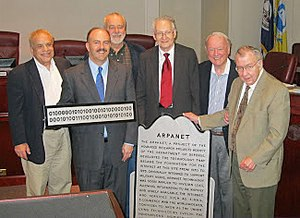 """Stephen J. Lukasik - Ceremony on 17 May 2011 at the Arlington County, Virginia Board to affix a plaque at DARPA headquarters commemorating the development of the ARAPANET. The binary sign spells out """"ARPANET.""""  Lukasik is in the middle of this picture, surrounded by former colleagues and Arlington County Virginia officials."""