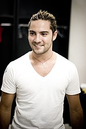 A picture of a man with his hair tied back and wearing a white T-shirt