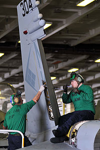 Defense.gov News Photo 110425-N-1004S-117 - Airman German Alulzo left strips sealant out of a rudder as Airman Kells Dean reinstalls a rudder bearing during phase A inspection on an F A-18C.jpg