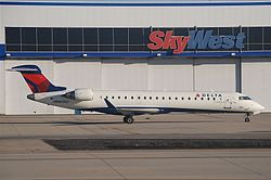Delta Connection CRJ700 in front of SkyWest hangar