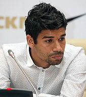 A colour photograph of Eduardo, at a press conference.