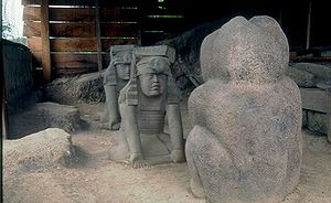"""El Azuzul - A photo of the sculptures in situ, as they were discovered, with the """"twins"""" facing off against the jaguar. The sculptures have since been moved to Xalapa."""