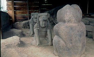 "El Azuzul - A photo of the sculptures in situ, as they were discovered, with the ""twins"" facing off against the jaguar. The sculptures have since been moved to Xalapa."