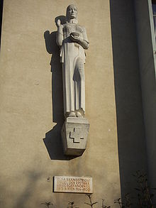 Life-size figure made of sandstone.  Emblem of the Red Cross as a relief on the base.
