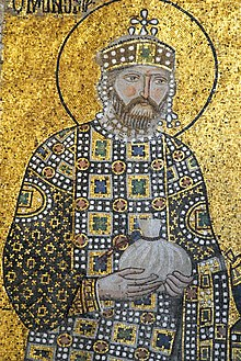 A mosaic with a background of gold showing a bearded Constantine wearing a crown and jeweled robes holding a small bag in his hands which is tied at the top