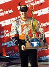 A man in his late twenties is wearing sunglasses along with orange racing overalls and is holding a trophy with both his hands.