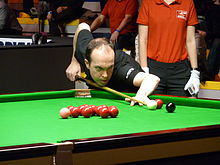 Fergal O'Brien leans across a snooker table holding his cue lining up a shot to a corner pocket