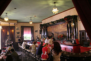 """Floridita - El Floridita bar. The bar """"patron"""" at center, below the wall-mounted photo, is a life-sized bronze statue of Ernest Hemingway"""