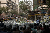 A large crowd stands behind metal fences around the base of a burned-out building, which is surrounded by many flowers and wreaths.