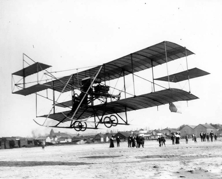 File:Fred J Wiseman piloting the first airplane (biplane) to land at the first air show at Olympia, held on the newly-built port fill (CURTIS 1203).jpeg