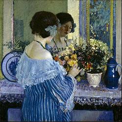 Frederick Carl Frieseke: Girl in Blue Arranging Flowers