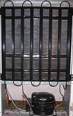 Componenti di un frigorifero domestico (visto da dietro). Sono visibili la serpentina di raffreddamento (in alto) e il compressore con relativo filtro (in basso).