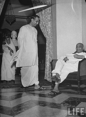 G. D. Birla - G. D. Birla with Vallabhbhai Patel, and Patel's daughter in the background, at Birla's residence, 1946. The statue is of Raja Baldeo Das Birla in Rajasthani turban