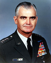 Middle-aged man with greying and receding dark hair combed back. He has drak bushy eyebrows. He wears a green dress uniform, with suit and tie, is clean-shaven, and has four stars on his shoulder to indicate his rank.