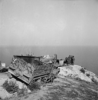 US troops with abandoned German equipment including an M3 halftrack May 1943. German M3 wreck2 Tunis May1943.jpg