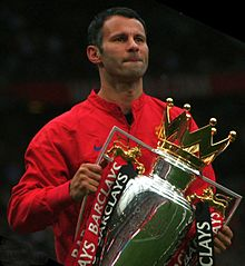 A head-and-torso photograph of a man with dark hair wearing a red tracksuit top. He is holding a large silver trophy with a gold crown on top. The trophy is decorated with one red ribbon and one black ribbon attached to each handle.