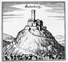 A medieval fortress stands on the peak of a hill, dominating the valley below it, and the river passing it in the distance; the fortress has a central keep (tower), and an elaborate ring of crenelated walls and narrow windows.  A road twists around the mountain to the gate.