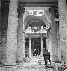 Photo noir et blanc, prise le 3 juillet 1945 à Berlin, montrant l'intérieur d'un hall du Reichstag en ruines. Au premier plan, un soldat, debout et de dos, regarde les innombrables graffitis écrits sur les colonnes de couleur claire du lieu.