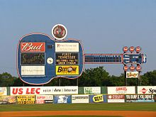 A view of the giant blue guitar-shaped scoreboard beyond the left-center field wall. Advertisements for local businesses adorn the guitar and the green outfield wall below.