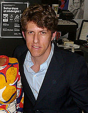 A brown-haired man in a navy blue coat