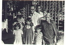 A black and white photo of H. R. Janardhana Iyengar with his wife, daughter and grandchildren in front of his house in the late 1970s
