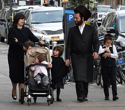 Hasidic family in Borough Park, Brooklyn. The man is wearing a shtreimel, and either a bekishe or a rekel. The woman is wearing a wig, called a sheitel, as she is forbidden to show her hair in public. Hasidic Family in Street - Borough Park - Hasidic District - Brooklyn.jpg