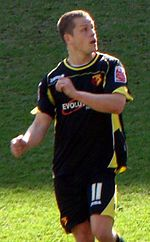 A man in a black football shirt and shorts, with yellow outline, standing on a grass field.