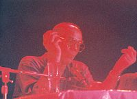 Photo of Thompson with sunglasses speaking into a microphone, but with red light