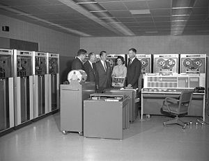 IBM 7090 - IBM 7090 operator's console at the NASA Ames Research Center in 1961, with two banks of IBM 729 magnetic tape drives. The card reader is in front of the man and woman at right.