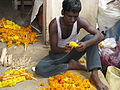 India - Faces - Young man patiently making flower garlands for sale (2566356389).jpg