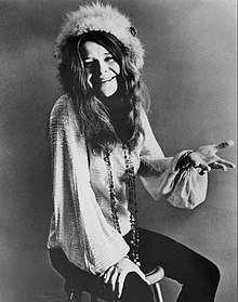 Janis Joplin sitting on a stool in a noir picture