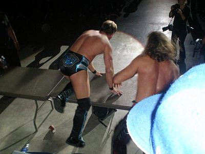 Chris Jericho (left) and Shawn Michaels on a table at a 2008 house show in Puerto Rico Jericho hbk table.jpg