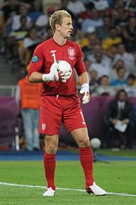 "Joe Hart – wearing a red long-sleeved goalkeeper's shirt of the England national football team featuring the ""Three Lions"" and Umbro logo, gold star and the number 1, along with red shorts and socks, and white cleats – looks towards the right while clutching a football in his right hand."