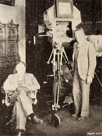 "John Arnold (cinematographer) - John Anderson (standing) with Lionel Barrymore on the set of the 1929 film, The Unholy Night, the housing around the camera is Arnold's invention, the ""bungalow"""
