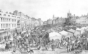 Very crowded market on a slope. At the left of the picture is a row of tall thin shops, and behind the market is another row of shops surrounding a tall church.