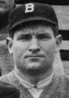 "A close-up of a man wearing a dark baseball cap with a white ""B"" on the center."