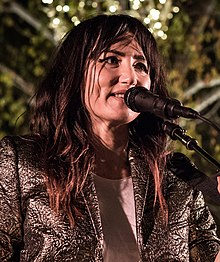 A photograph of Tunstall smiling, looking away from the camera. A microphone is positioned in front of her face.