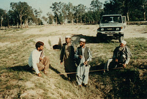 Ahmed Khadr - Khadr's Toyota Landcruiser in background; workers measuring an irrigation canal.