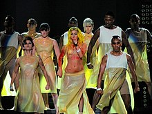 A group of dancers on stage, wearing light yellow colored dresses. In their middle is a blond singer wearing the same dress, with blotches of red color all over her body