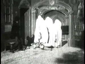 The Haunted Castle (1896 film) - A cavalier is subdued by spectres (centre) summoned by the Devil (left).