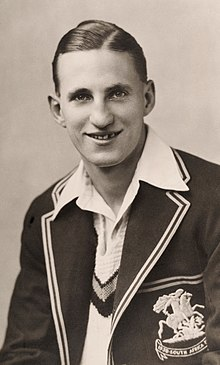 A black and white photograph of a young man wearing cricket whites and a blazer